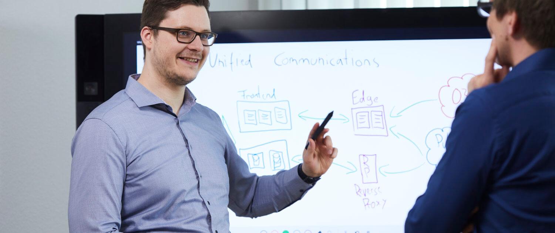 Der moderne Arbeitsplatz - Mitarbeiter können wie hier am Surface Hub orts- und zeitunabhängig Dokumente bearbeiten und kommunizieren.